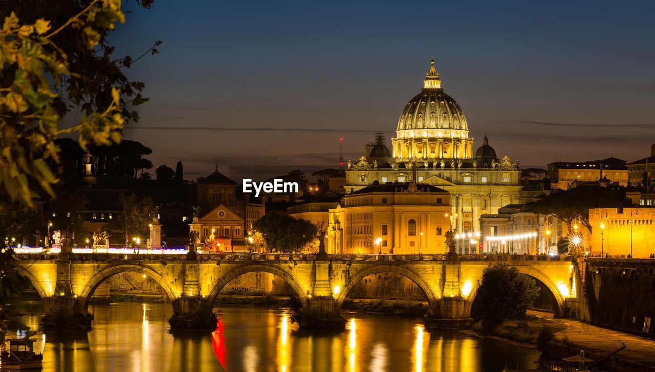 Illuminated Arch Bridge Over River Against Buildings In City