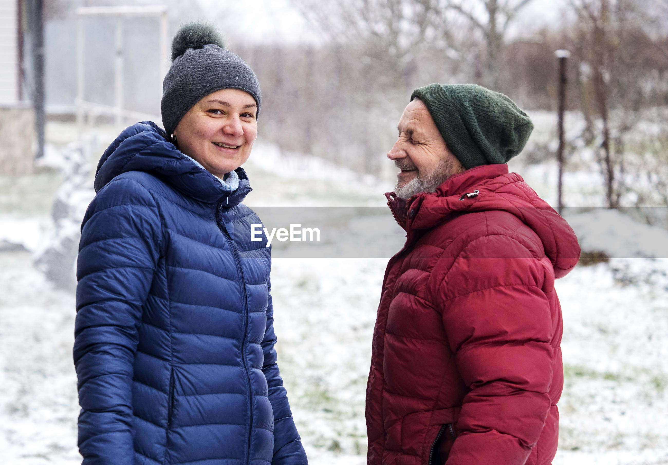Portrait of mature woman wearing warm clothing standing with father outdoors during winter