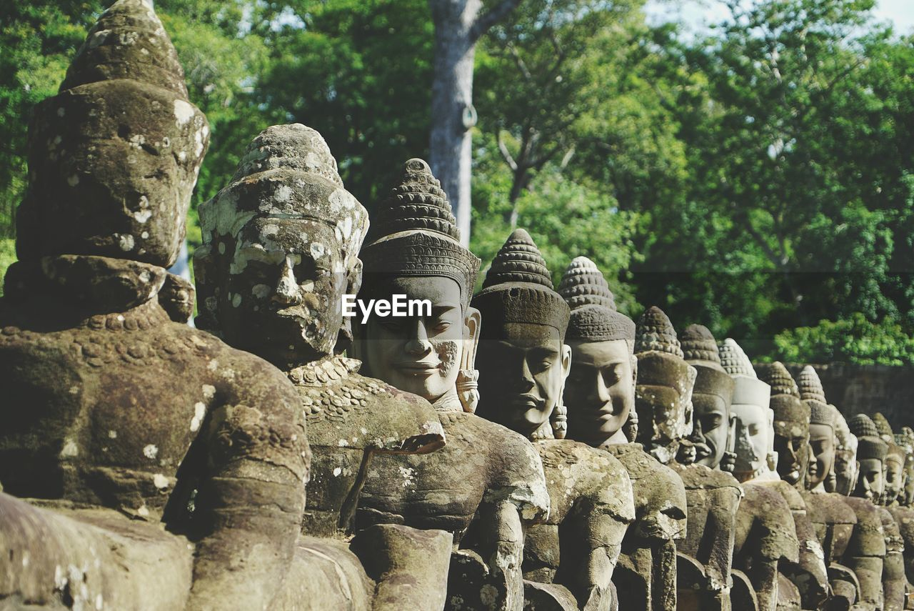 Close-Up Of Buddha Statues In Row Against Trees