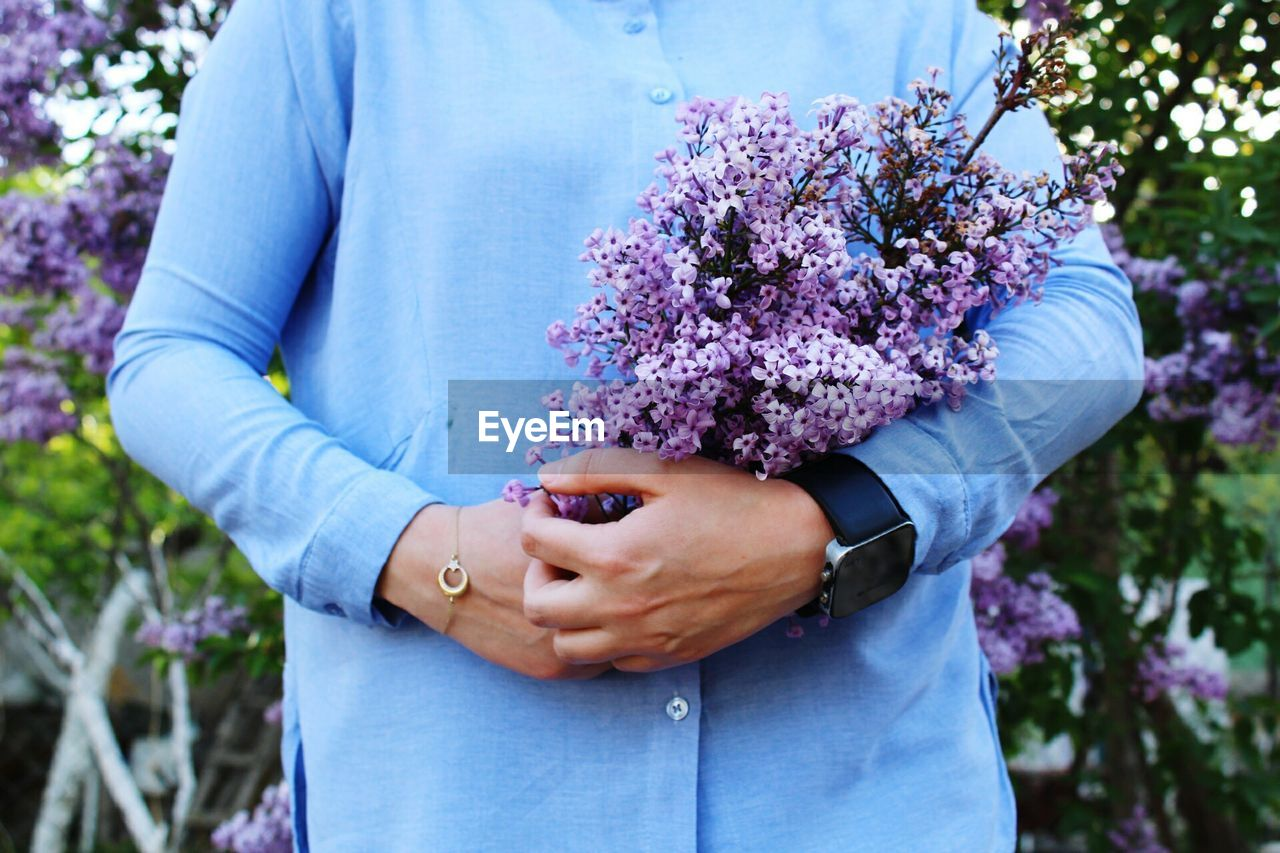 Midsection of woman holding purple flowers outdoors
