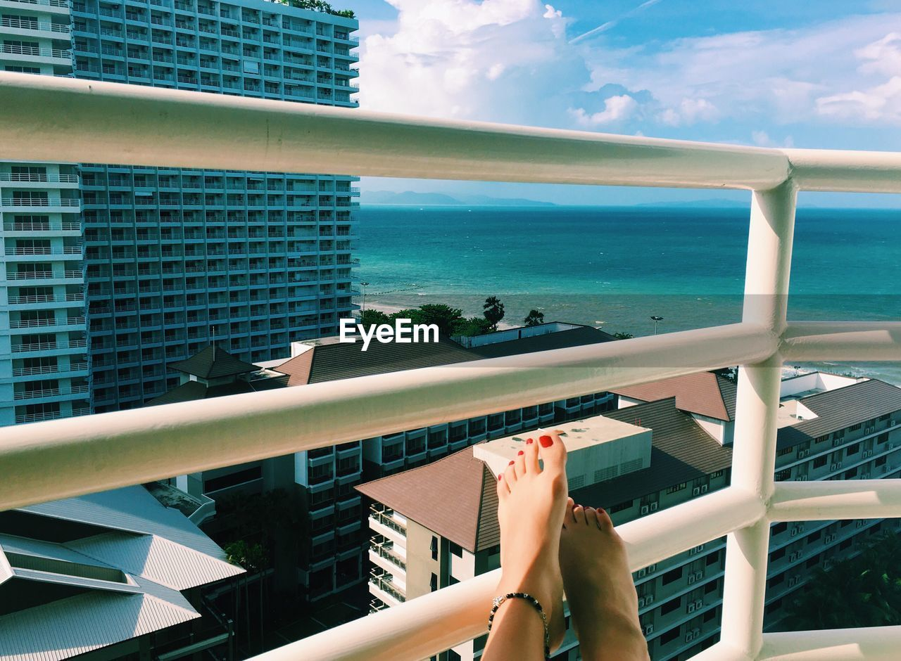 Low section of woman in red nail polish on railing against sea on sunny day