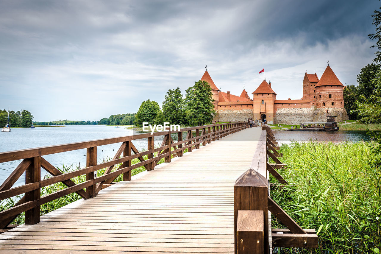architecture, built structure, sky, water, wood - material, cloud - sky, direction, nature, the way forward, railing, plant, no people, day, building exterior, building, tree, beauty in nature, outdoors, lake, wood paneling