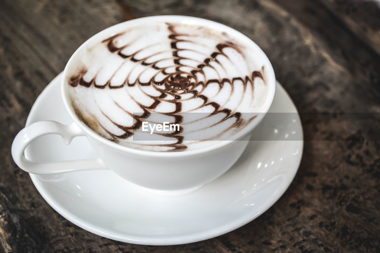 Close-Up Of Coffee Cup In Saucer On Table