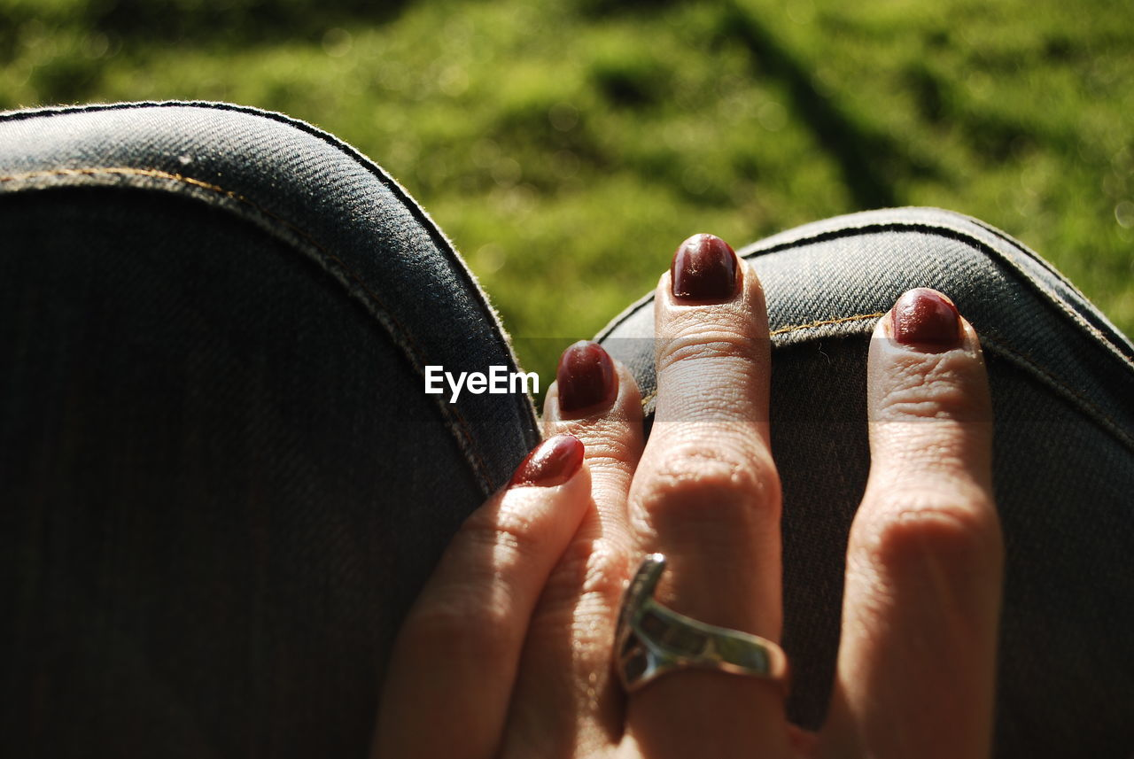 Cropped hand of woman touching seat outdoors