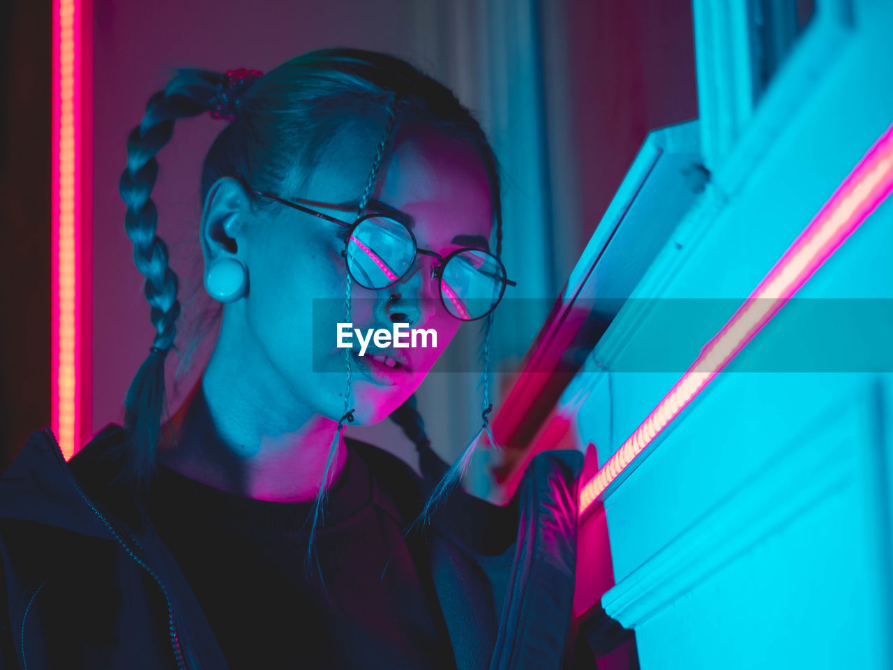 Close-Up Of Young Woman Wearing Eyeglasses While Standing Outdoors At Night