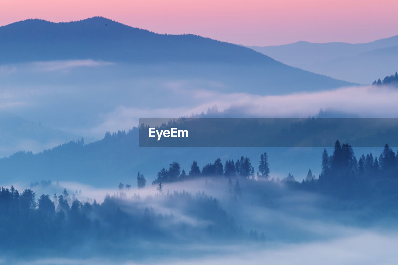 Scenic view of fog covered mountains against sky during sunrise