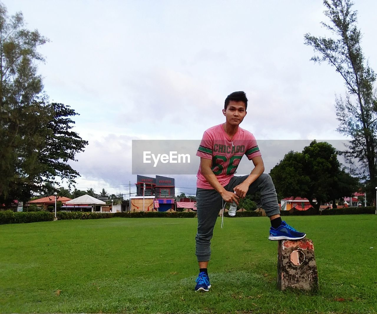 tree, leisure activity, full length, lifestyles, one person, grass, sky, real people, day, sport, looking at camera, cloud - sky, outdoors, young men, front view, casual clothing, standing, park - man made space, portrait, young adult, growth, skill, playing, happiness, boys, smiling, men, nature, people