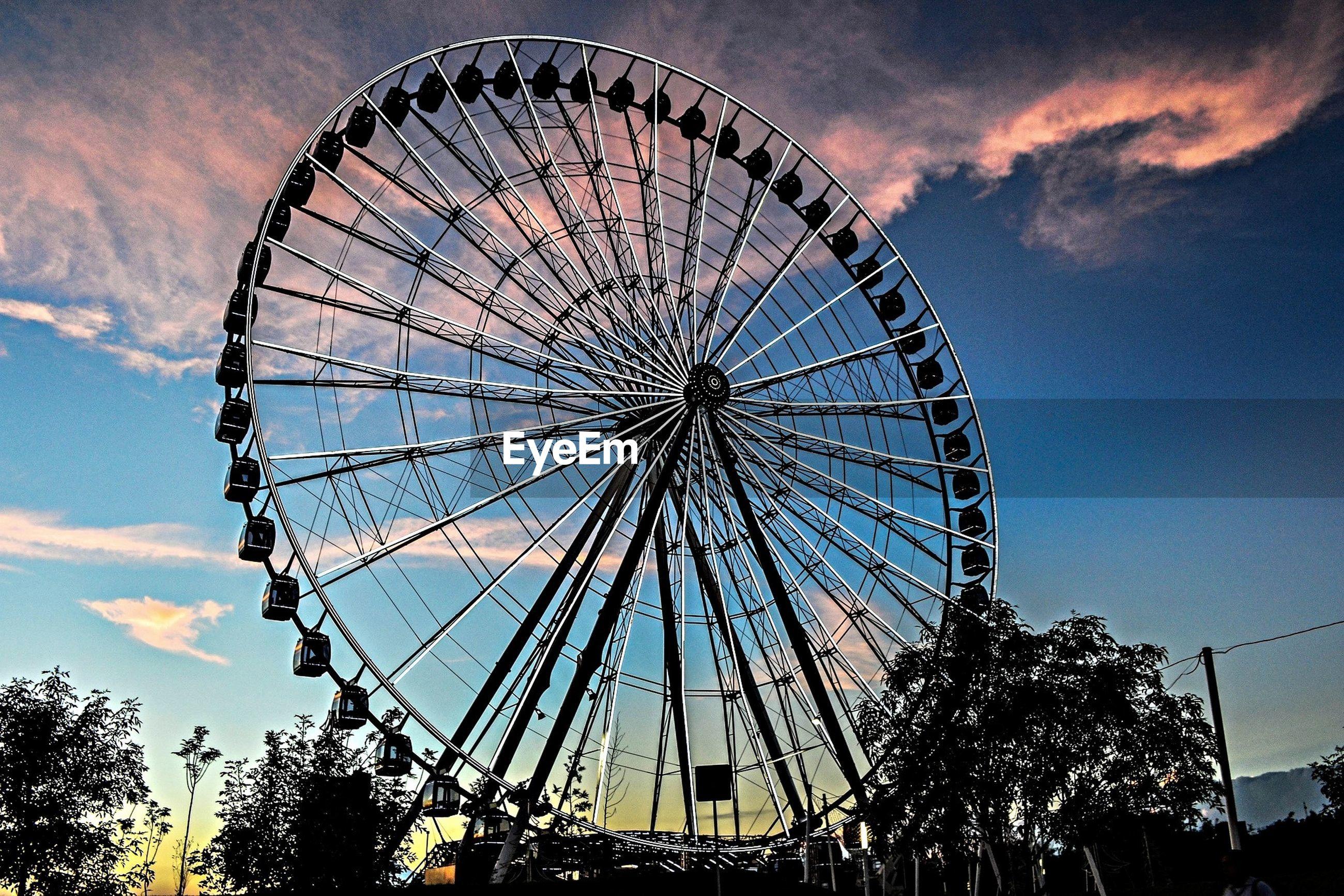 ferris wheel, amusement park, amusement park ride, arts culture and entertainment, low angle view, sky, cloud - sky, big wheel, silhouette, fun, large, enjoyment, cloud, fairground, fairground ride, outdoors, built structure, leisure activity, dusk, circle