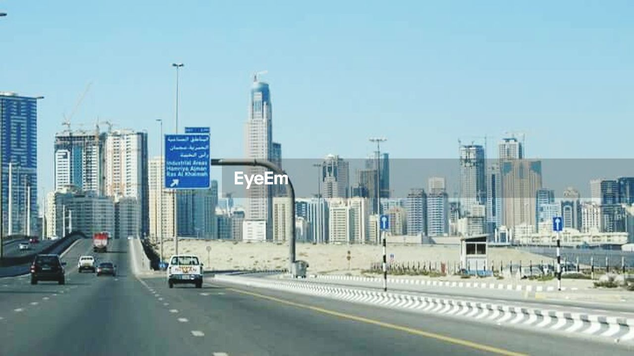 skyscraper, architecture, city, transportation, building exterior, modern, road, car, built structure, day, land vehicle, outdoors, no people, urban skyline, travel destinations, cityscape, sky, clear sky