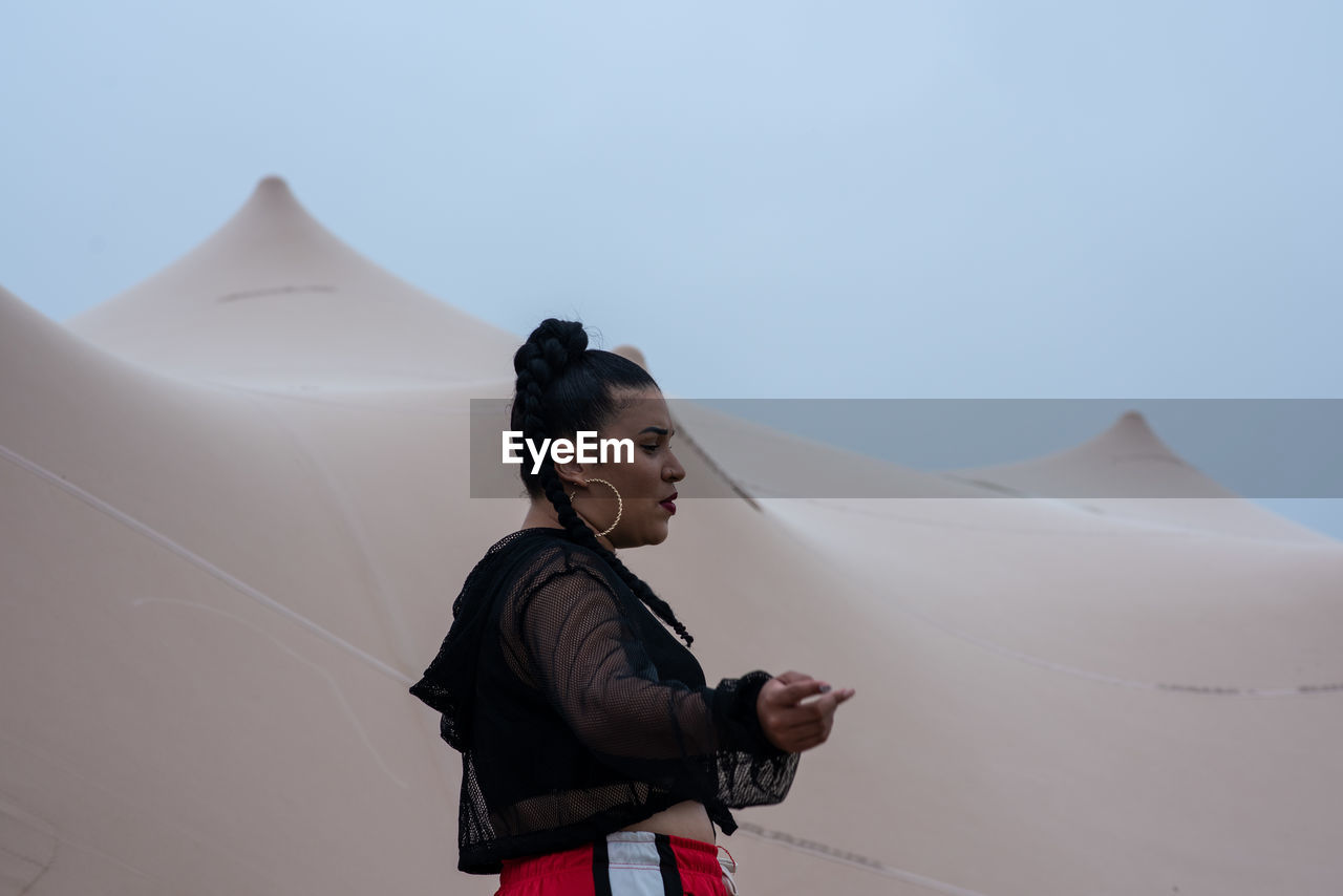 Side view of young woman standing at sand dune against clear sky