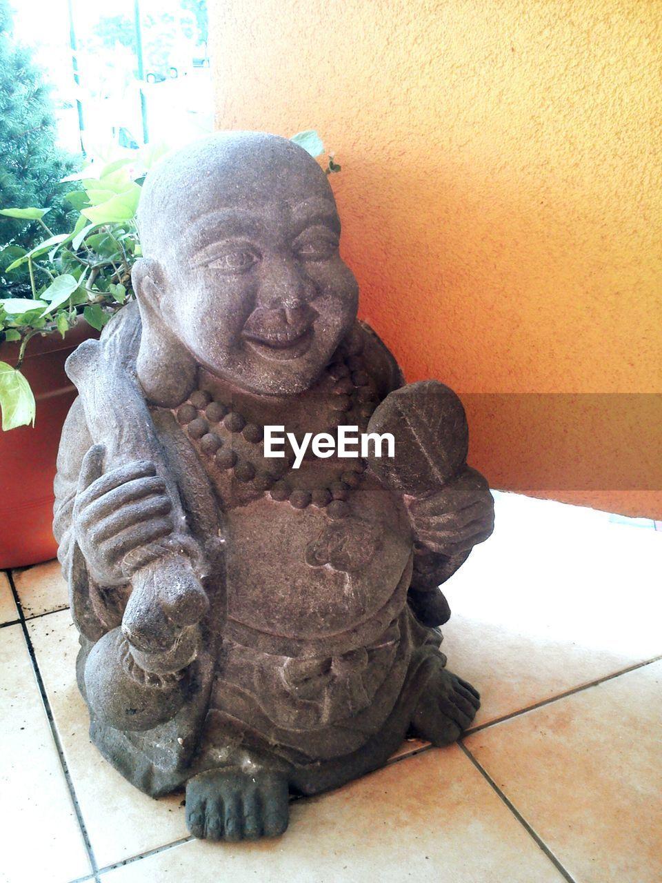 Laughing Buddha Sculpture On Flooring