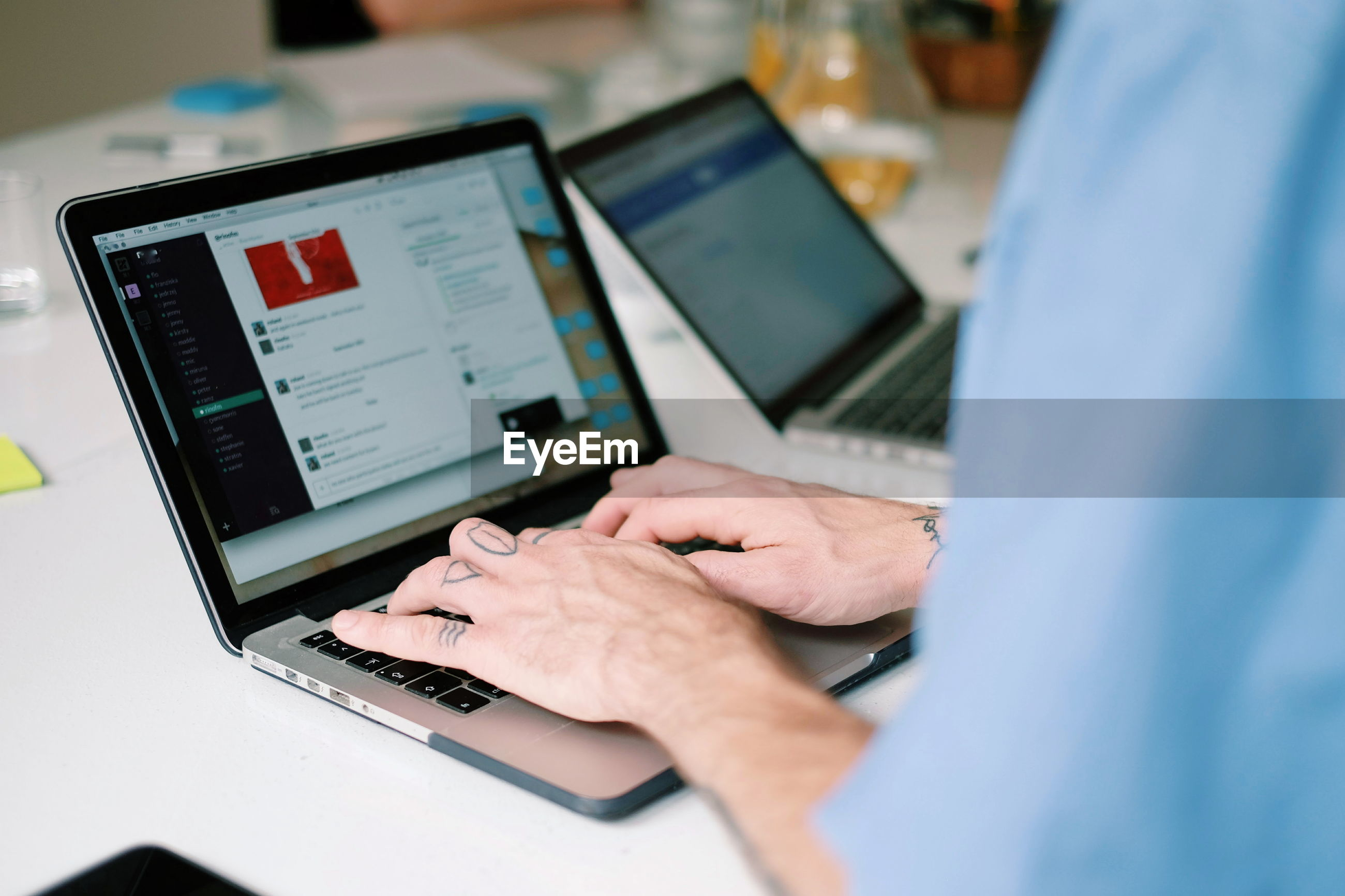 Close-up of man using laptop in office