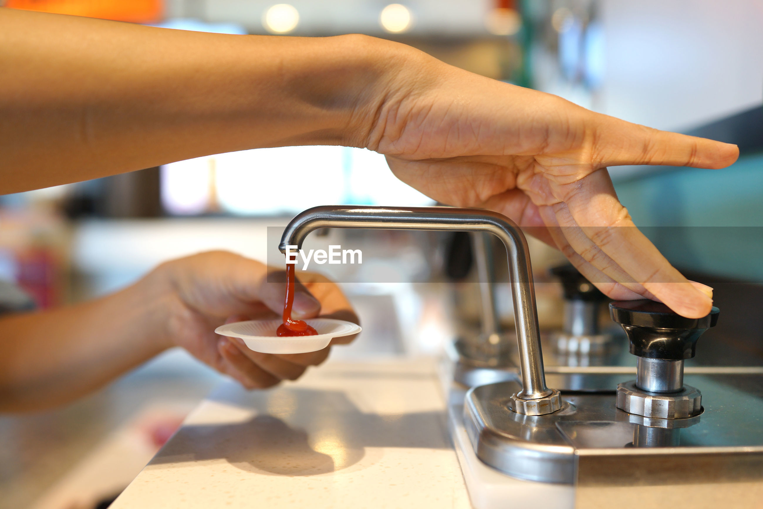 Cropped image of person pouring tomato sauce in cup