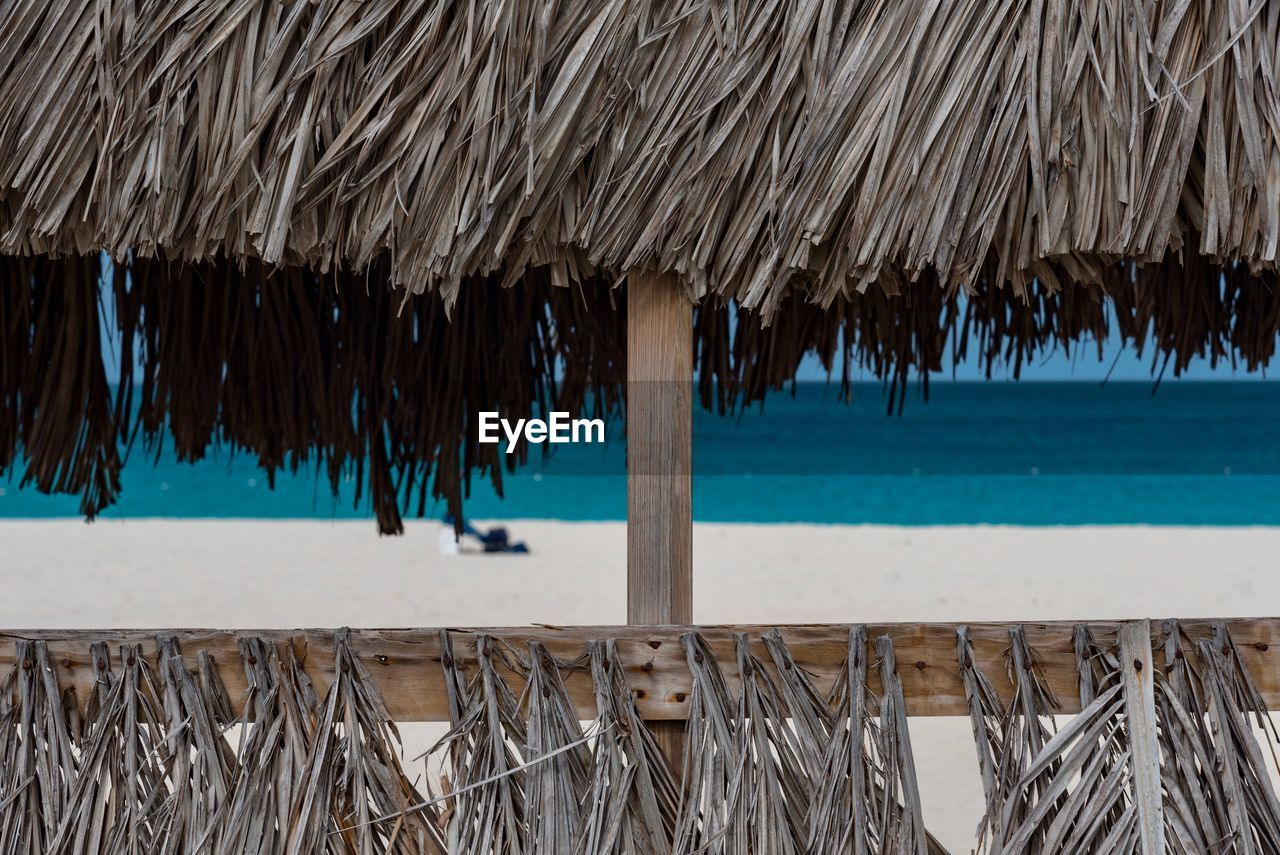 thatched roof, water, beach, roof, shelter, outdoors, nature, day, beauty in nature, no people
