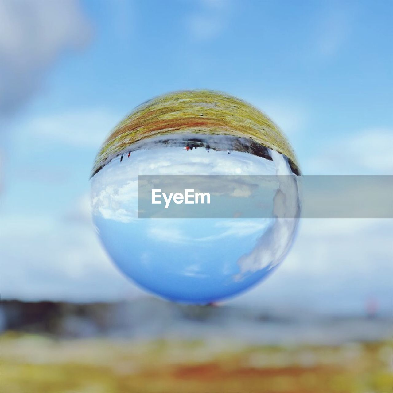 sphere, crystal ball, close-up, focus on foreground, single object, no people, crystal, sky, shiny, ball, blue, outdoors, marbles, fragility, day, bubble wand
