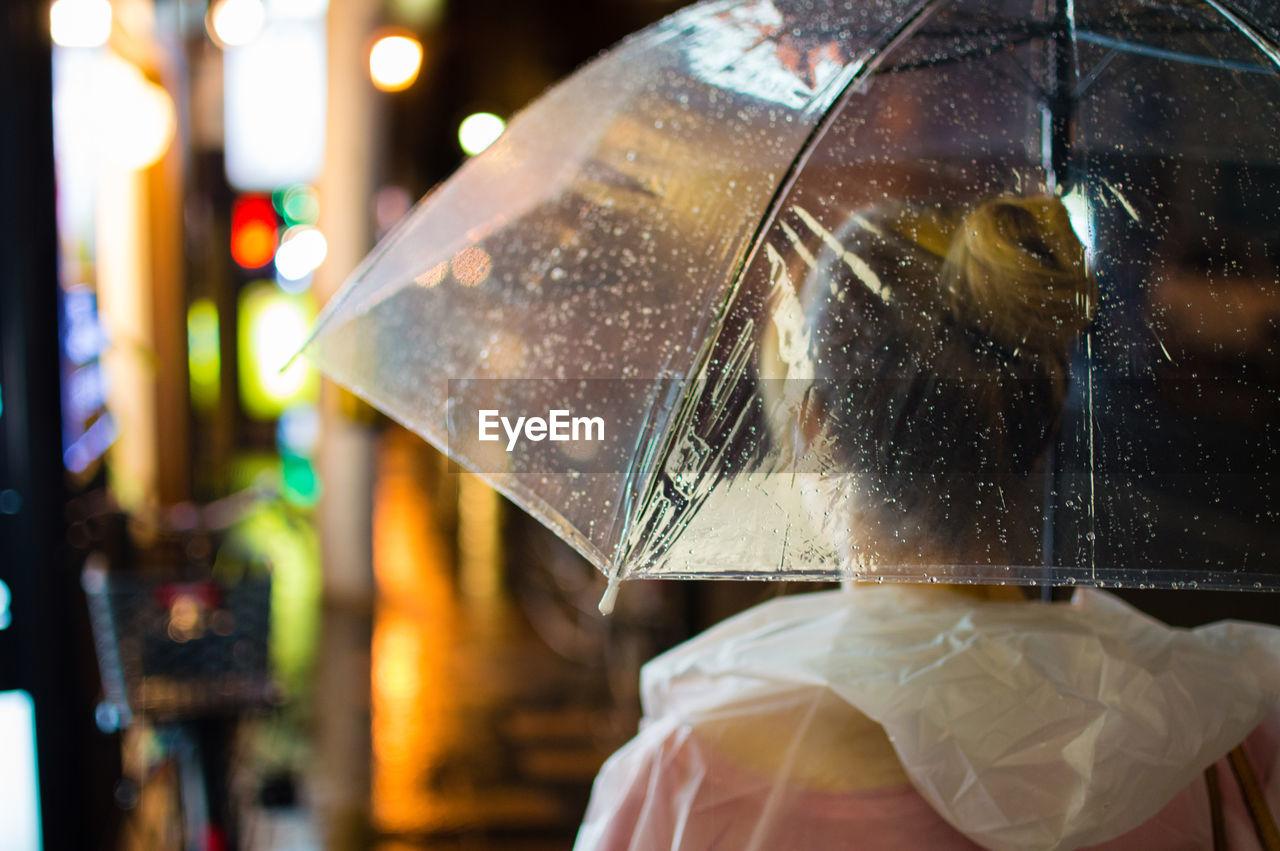 Rear View Of Woman In Umbrella During Rainy Season