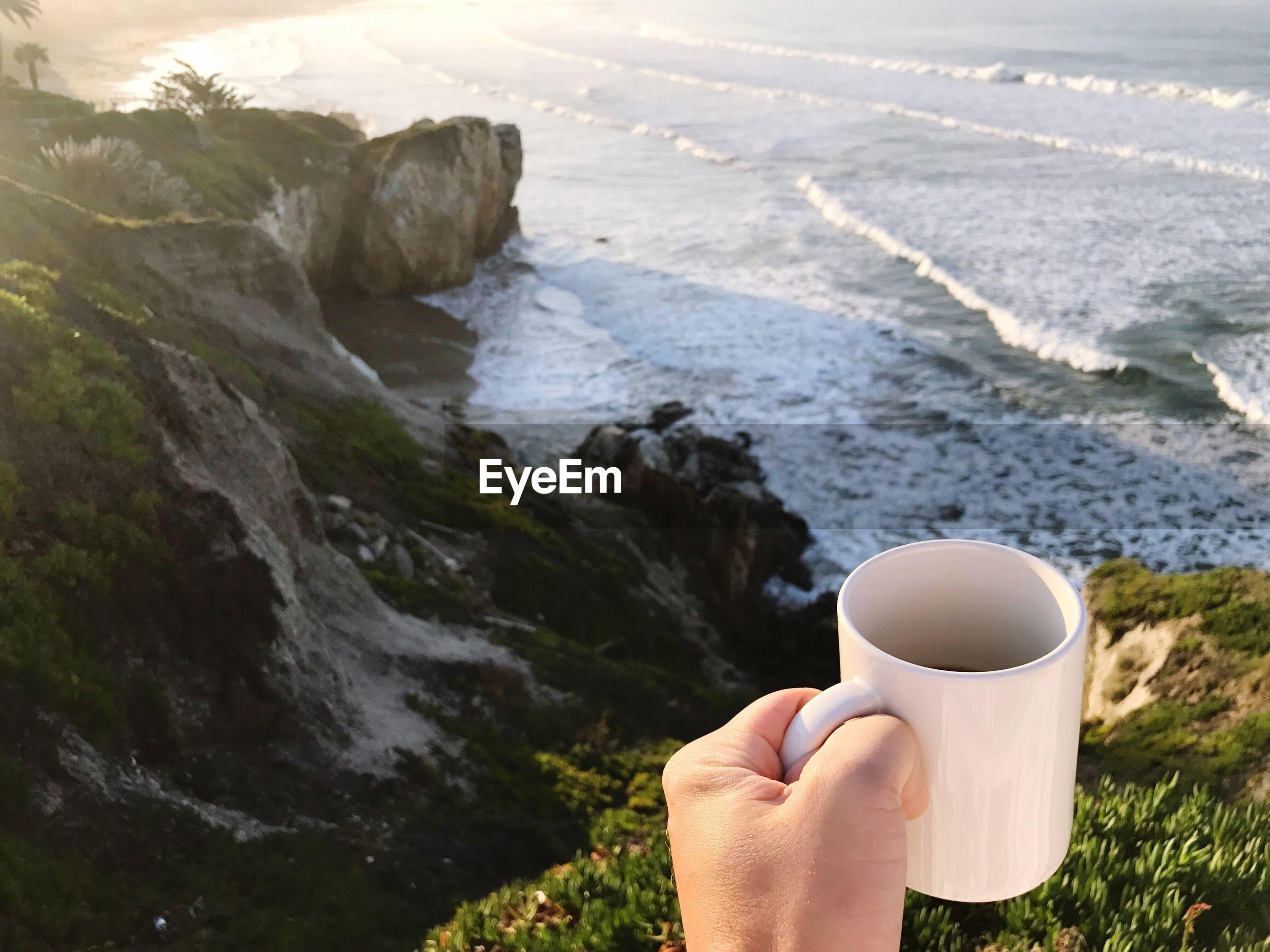 Cropped image of hand holding coffee mug against sea