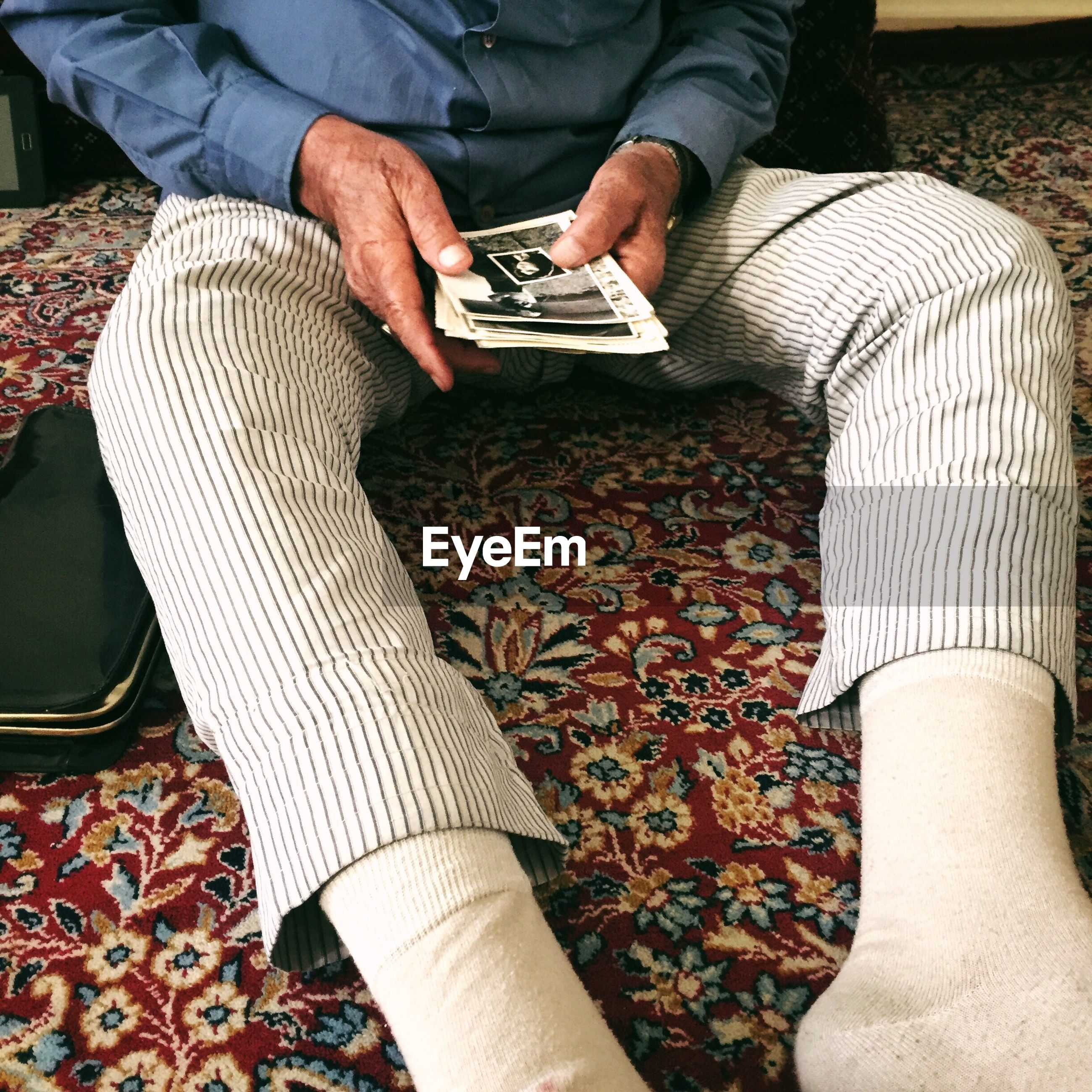 LOW SECTION OF MAN SITTING ON FLOOR