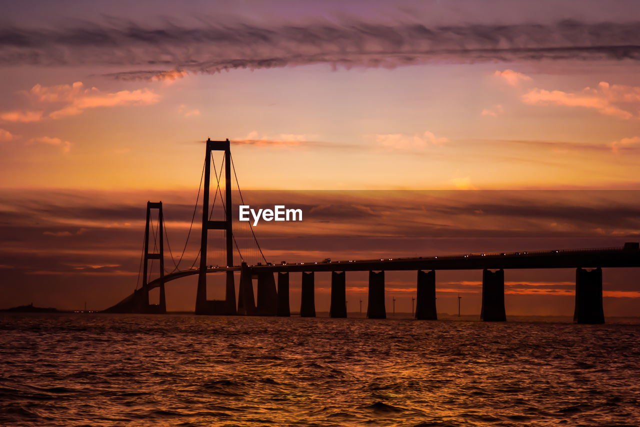 sunset, bridge - man made structure, water, connection, sky, sea, cloud - sky, suspension bridge, built structure, orange color, scenics, no people, nature, architecture, travel destinations, outdoors, beauty in nature, day