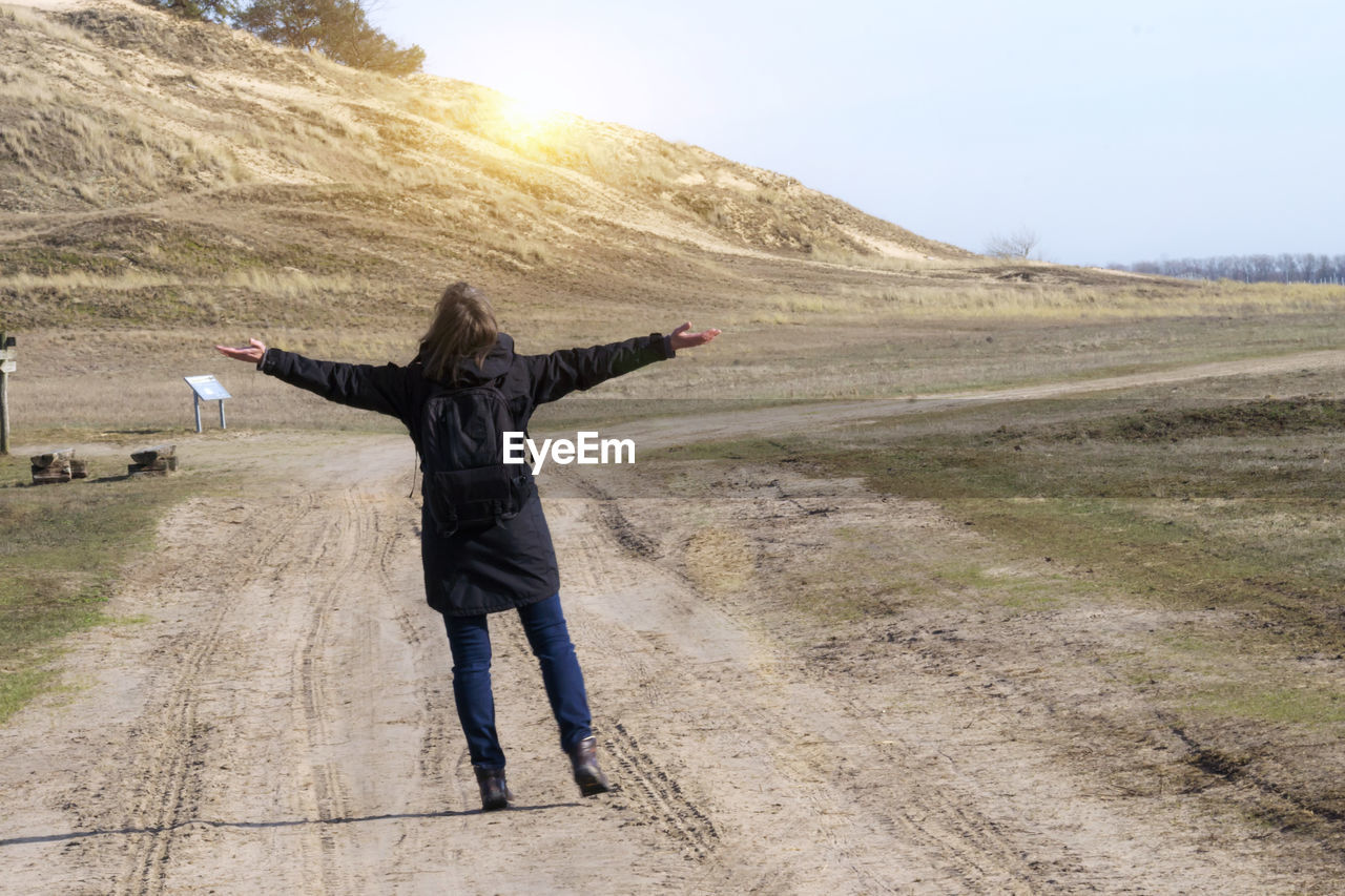 one person, leisure activity, real people, full length, human arm, lifestyles, arms outstretched, landscape, environment, limb, standing, adult, scenics - nature, day, nature, sky, rear view, casual clothing, men, outdoors, arms raised, warm clothing, freedom