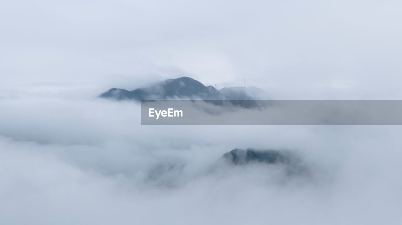 cloud - sky, beauty in nature, sky, scenics - nature, mountain, tranquil scene, fog, tranquility, no people, nature, day, non-urban scene, outdoors, environment, idyllic, mountain range, cloudscape, majestic, covering, hazy