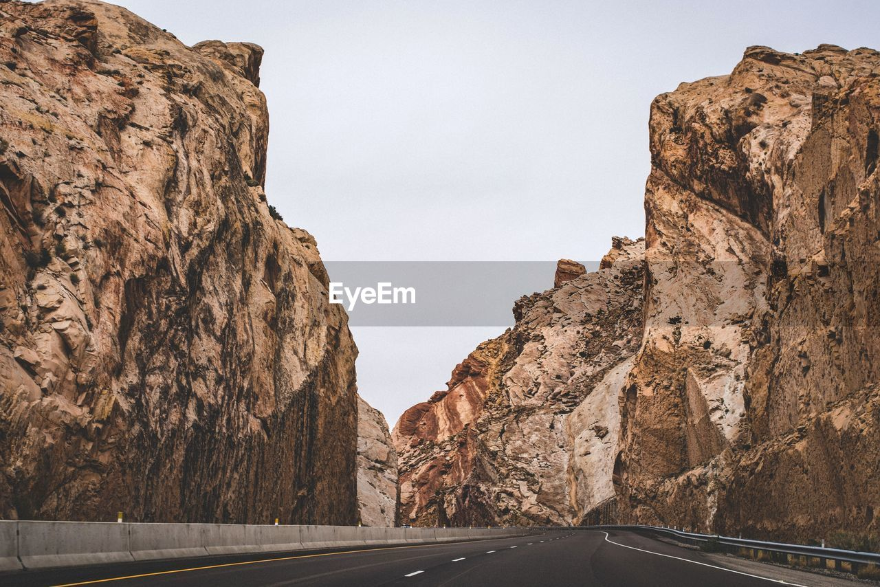 Empty road amidst rocky cliffs against sky