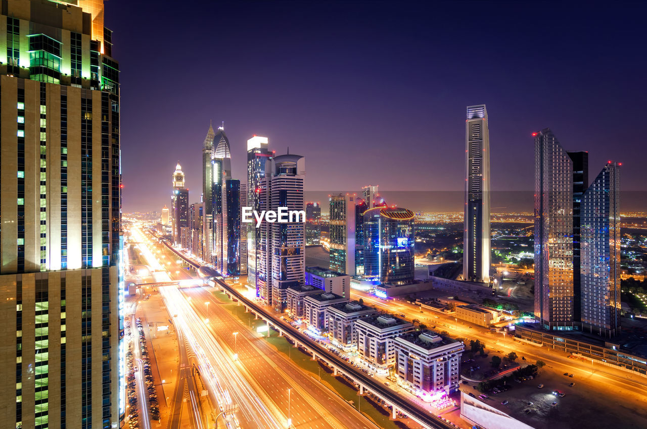Light Trails Of Dubai Downtown Skyline By Buildings Against Sky At Night