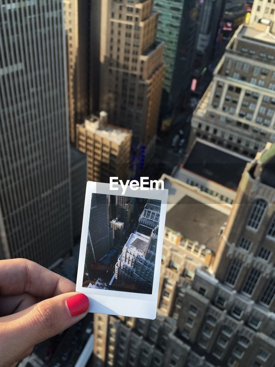 Close-up of female hand holding instant camera picture against buildings