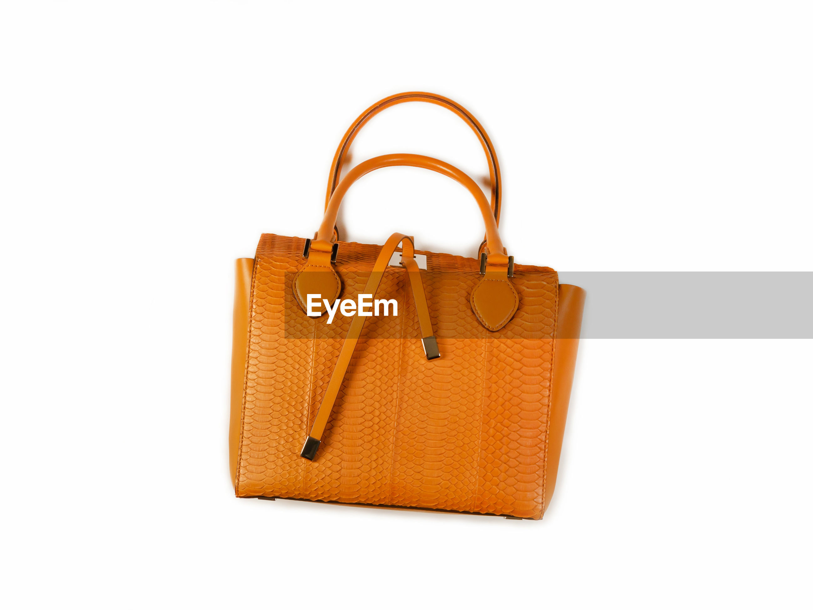 Close-up of orange purse over white background