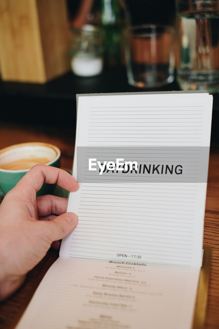 Cropped hand of holding book with text on table