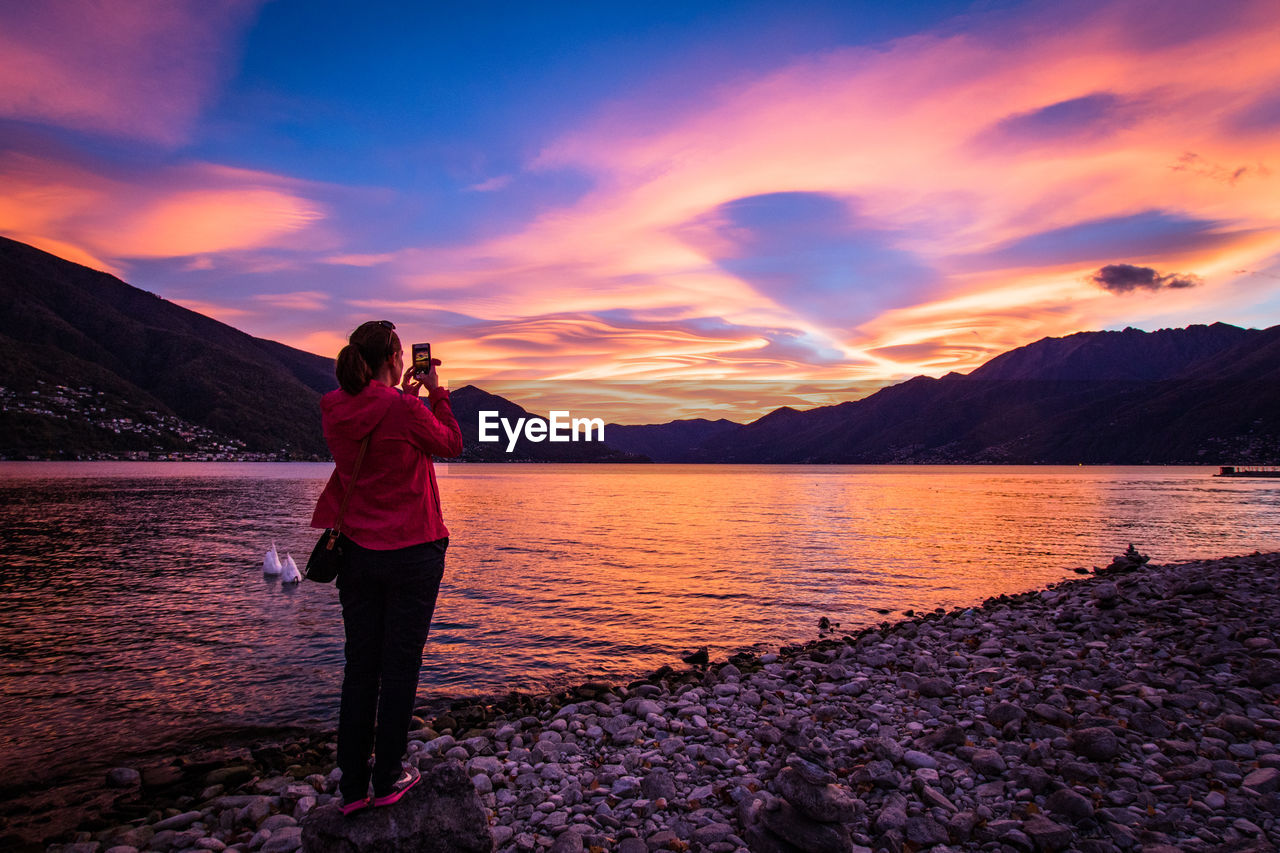 Woman Photographing Through Mobile Phone At Lake Against Sky During Sunset