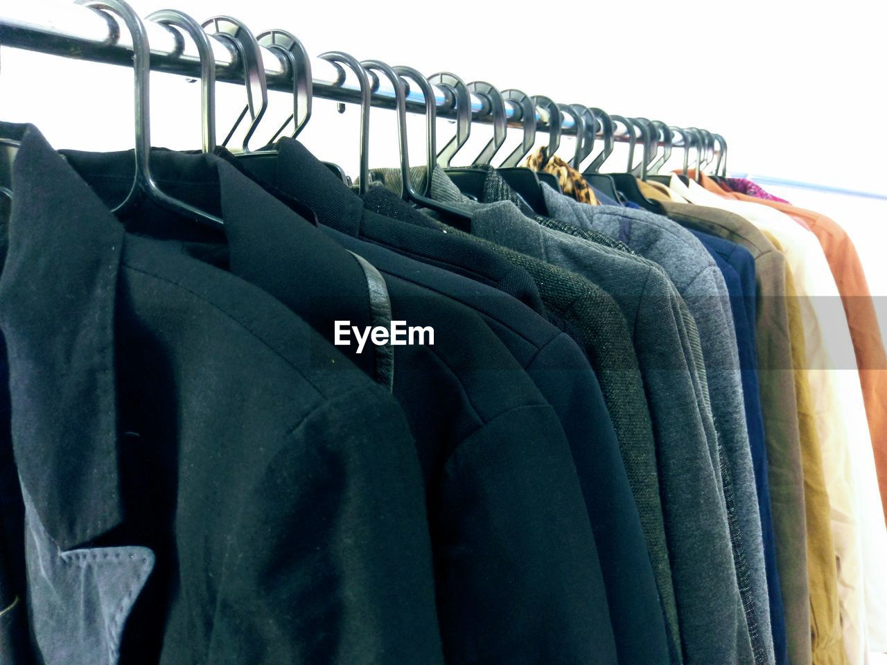MIDSECTION OF CLOTHES HANGING ON RACK