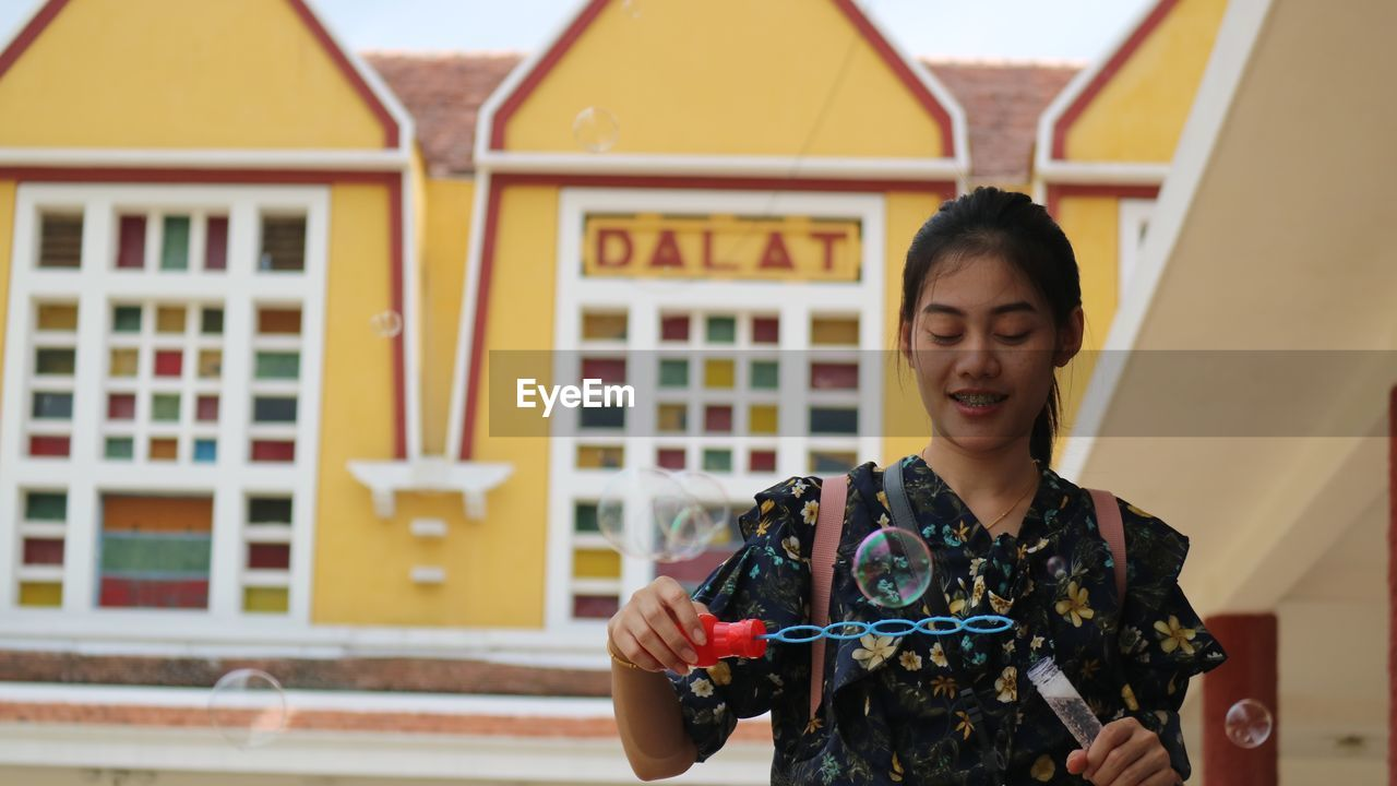 Woman holding bubble wand against building