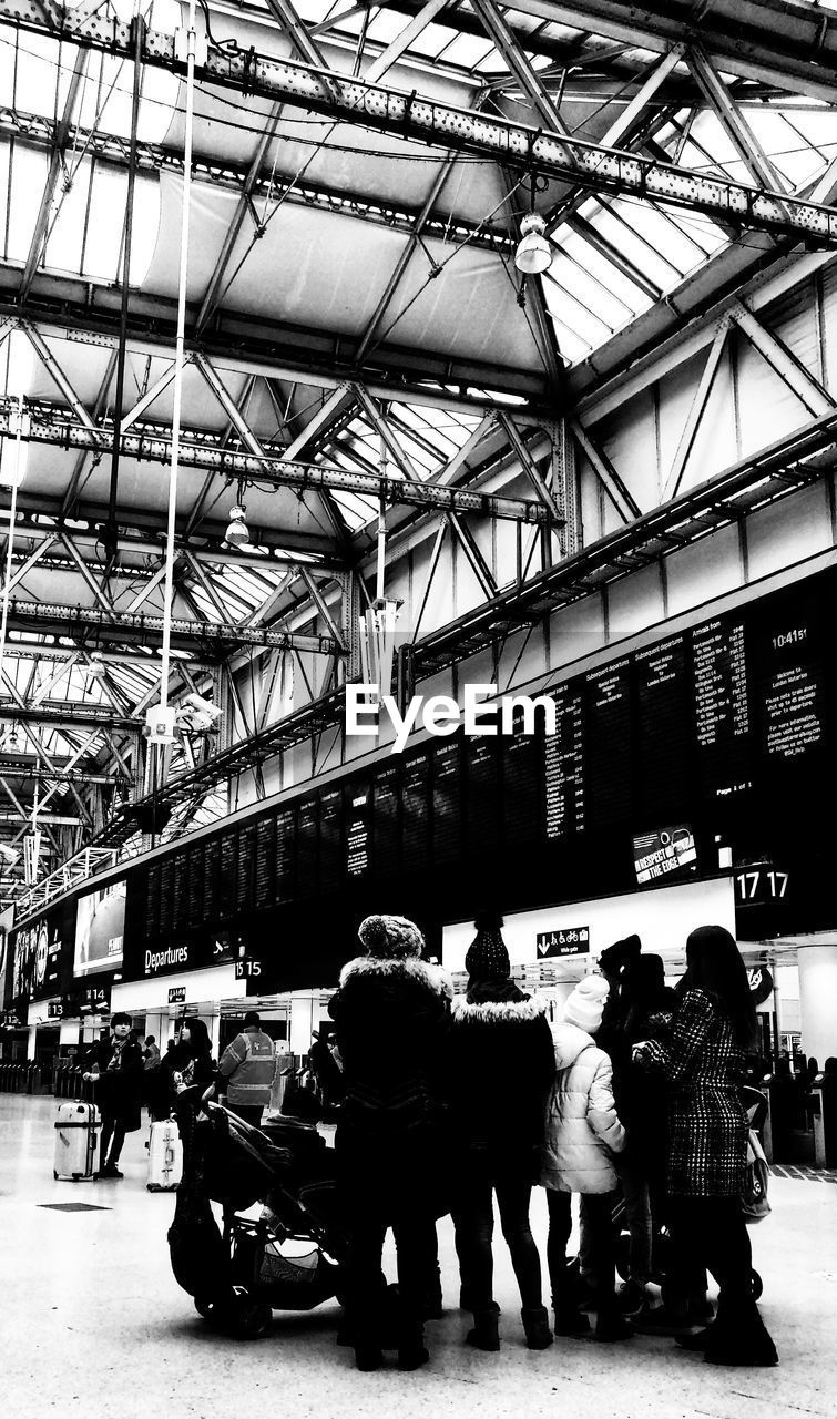 group of people, real people, men, built structure, architecture, women, text, people, crowd, city, adult, lifestyles, day, indoors, transportation, rear view, leisure activity, waiting, ceiling, station