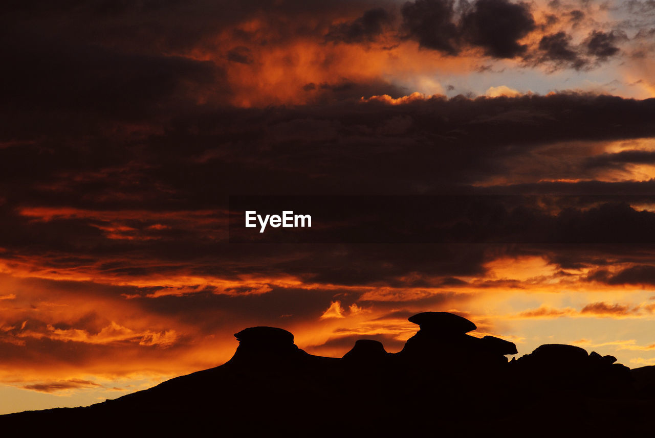 Silhouette rock formations against cloudy sky during sunset