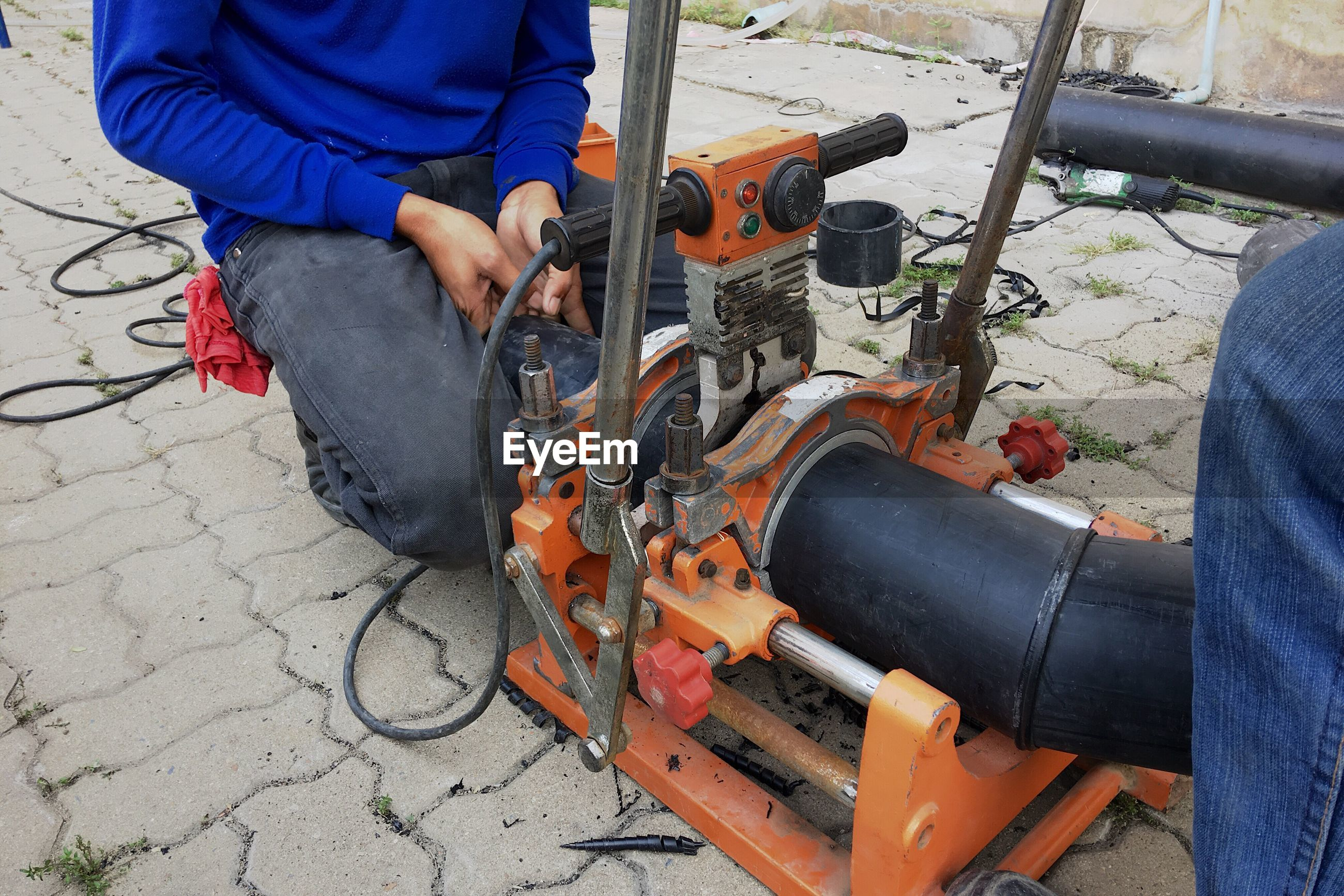 Midsection of man crouching by machinery on footpath