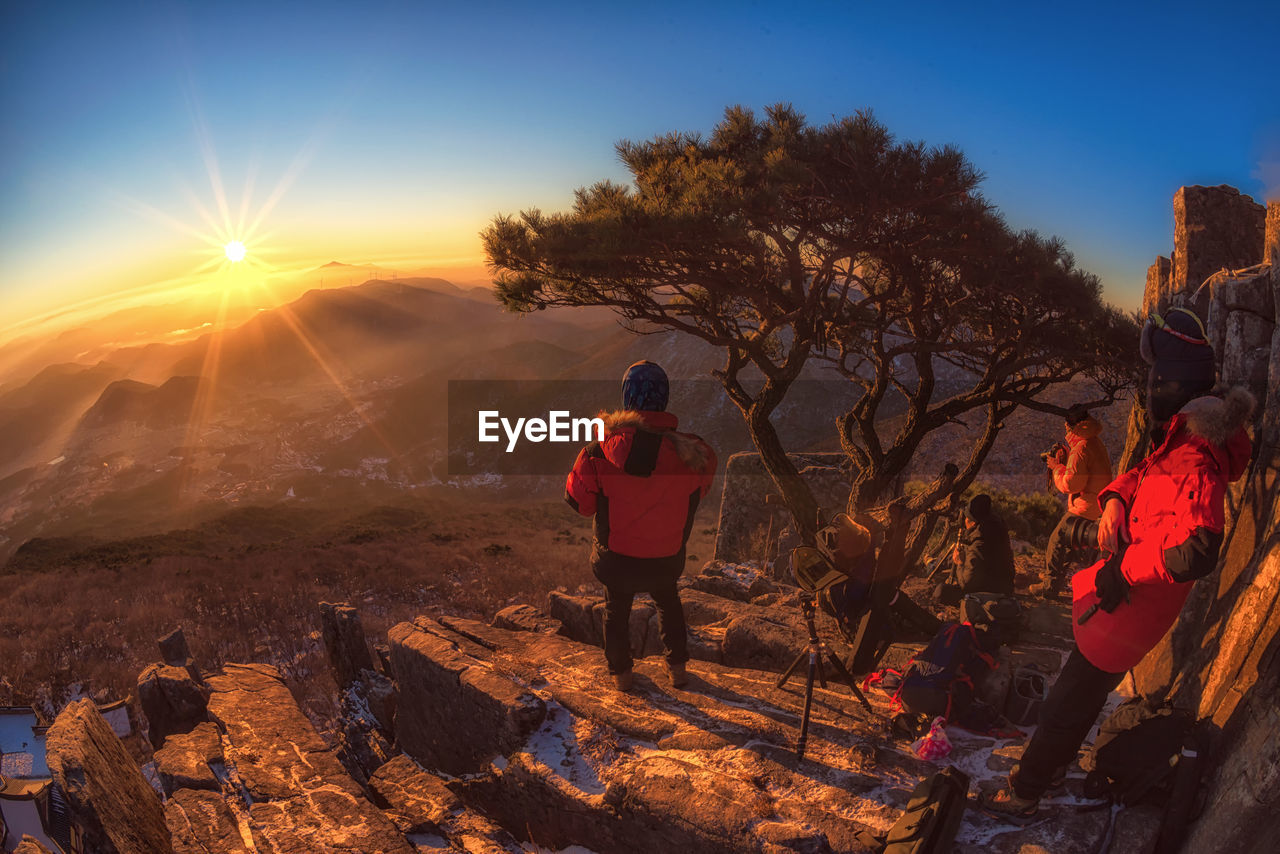 real people, sunset, nature, lifestyles, standing, leisure activity, rock - object, beauty in nature, sky, outdoors, sunlight, full length, one person, scenics, tree, men, day, people