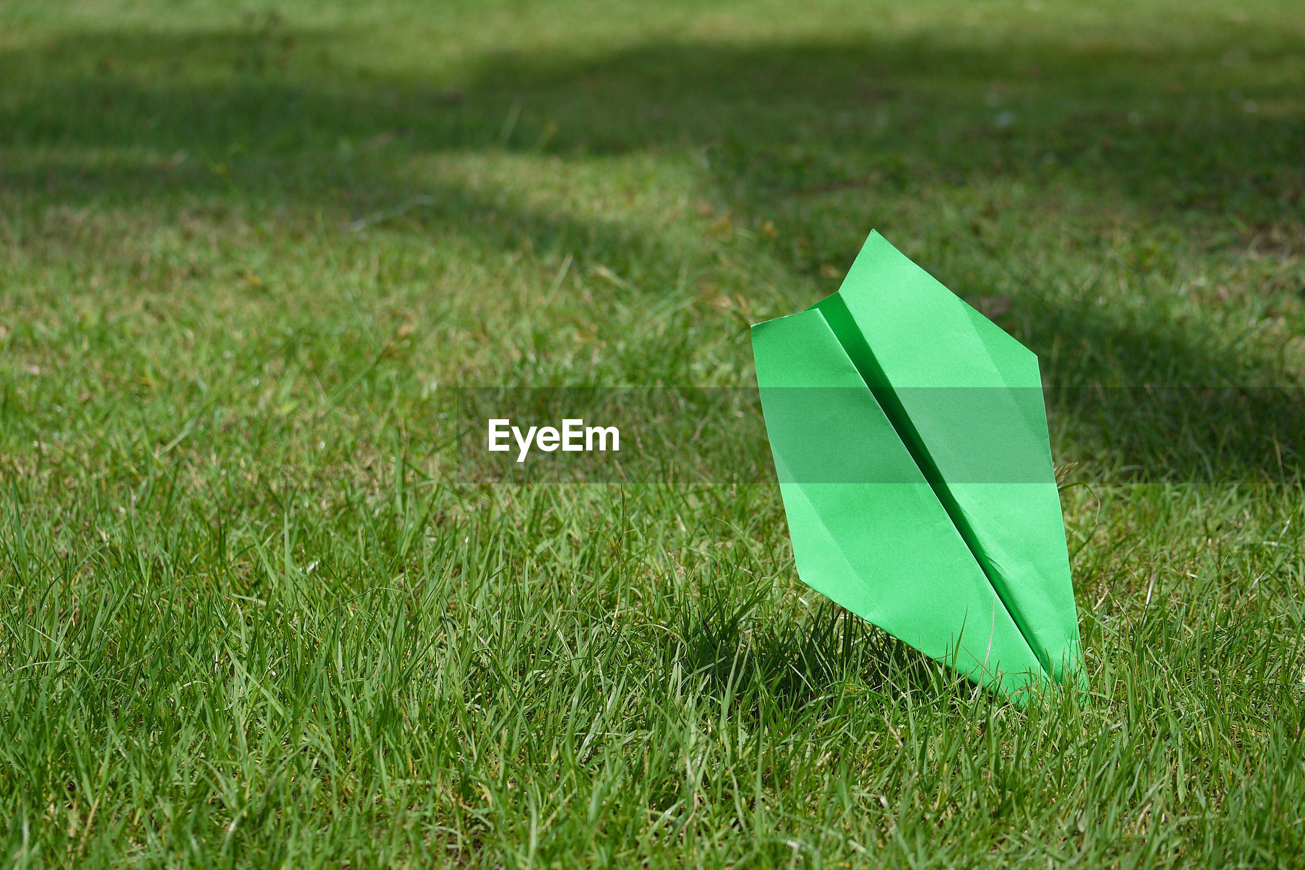 Green paper airplane on grassy field