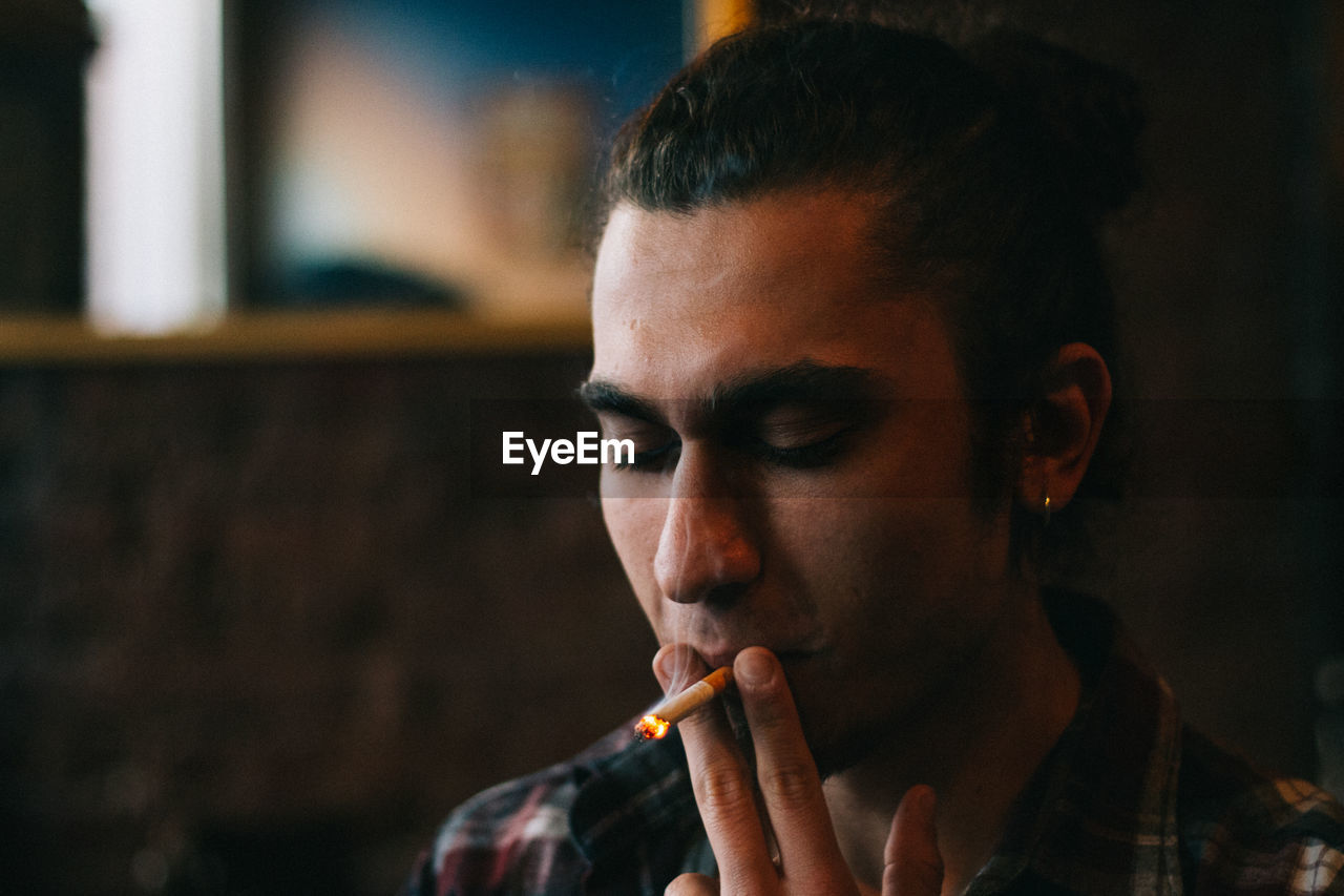 Close-Up Of Young Man Smoking Cigarette At Restaurant