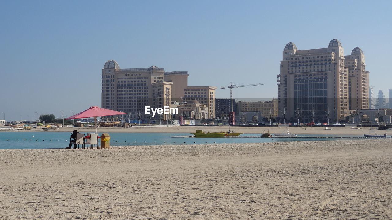 Katara Beach And Buildings Against Clear Sky