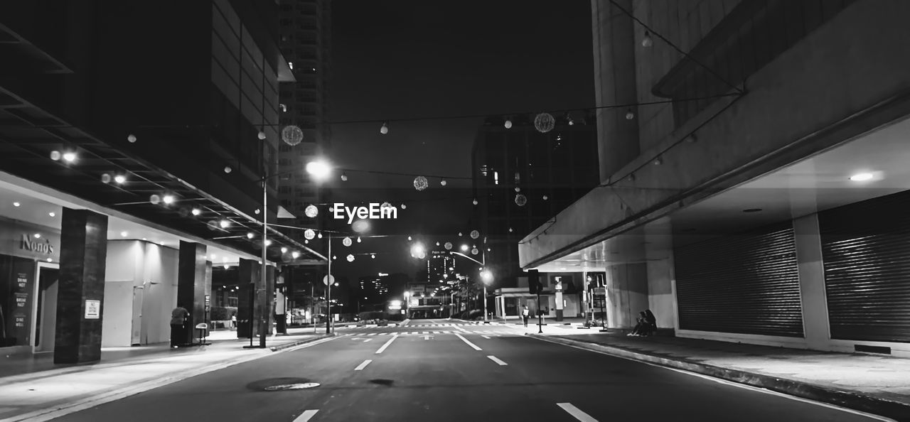 EMPTY ROAD AMIDST BUILDINGS AT NIGHT