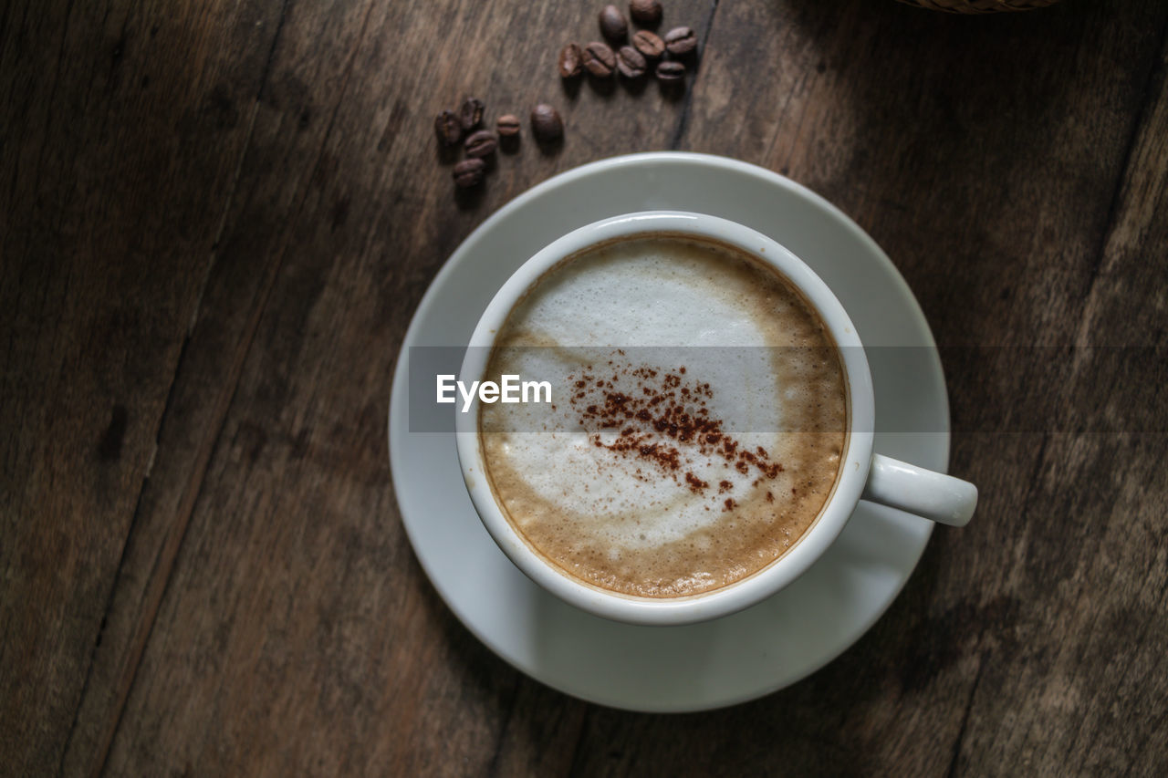 cup, food and drink, drink, refreshment, coffee - drink, coffee, coffee cup, mug, still life, frothy drink, table, saucer, freshness, hot drink, crockery, high angle view, indoors, wood - material, cappuccino, no people, latte, non-alcoholic beverage, froth