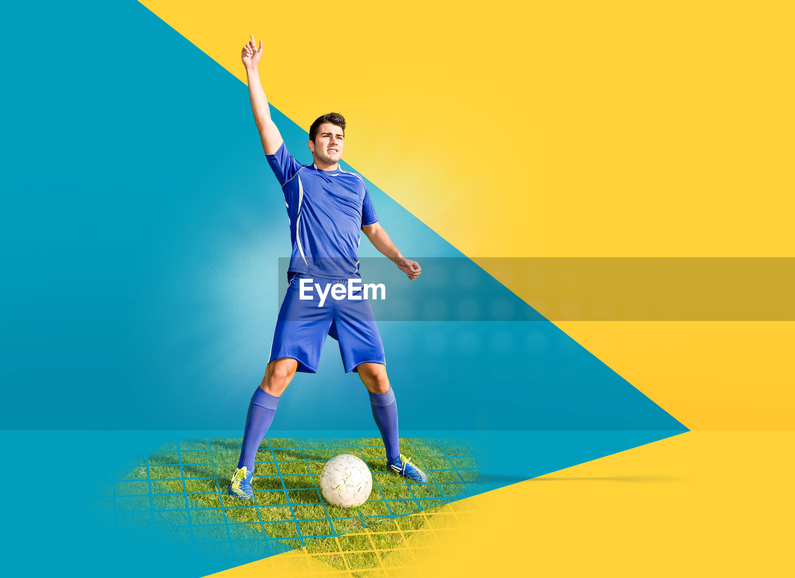 Soccer player with ball standing against colored background