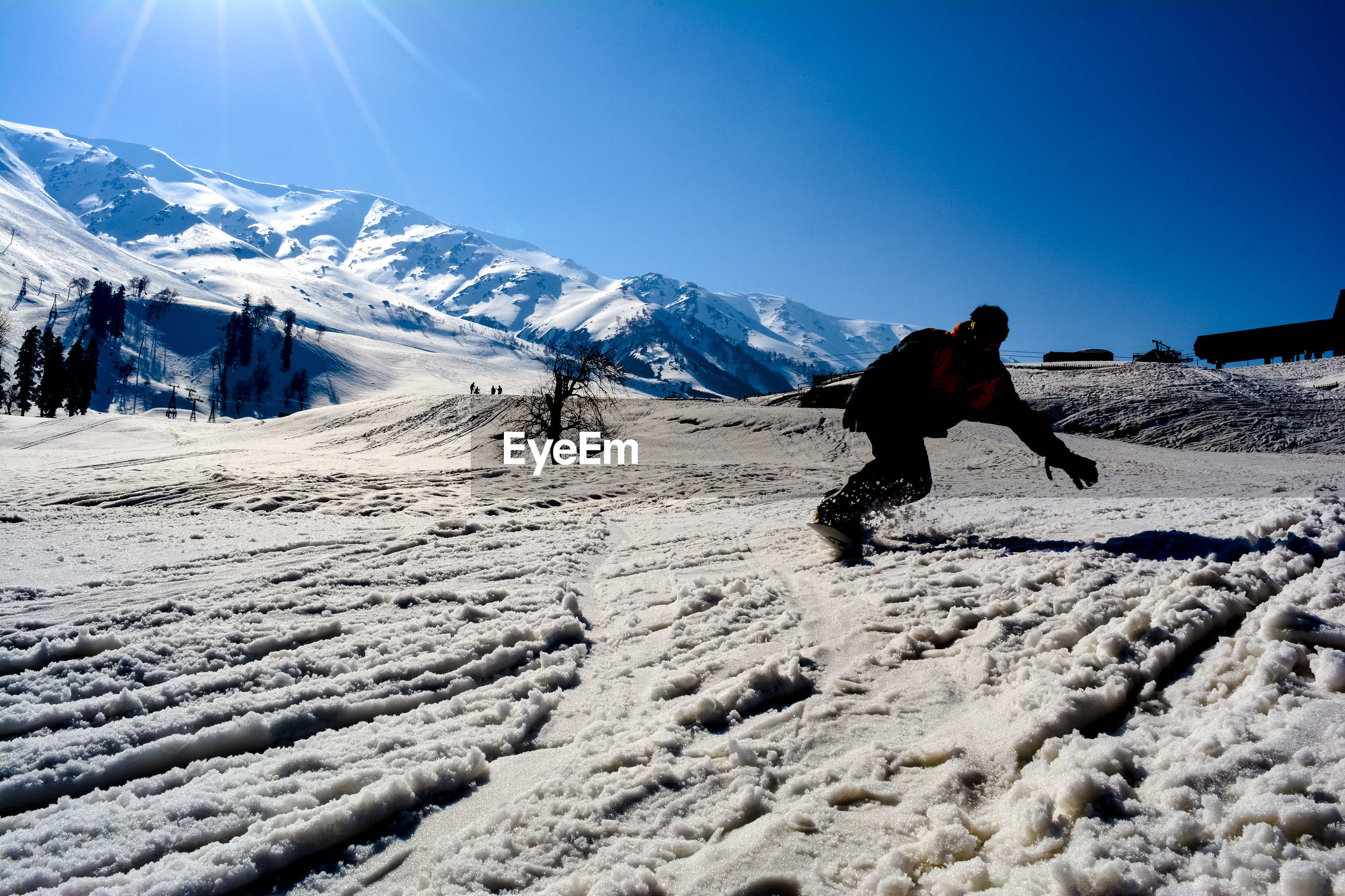 Man snowboarding on mountain against blue sky