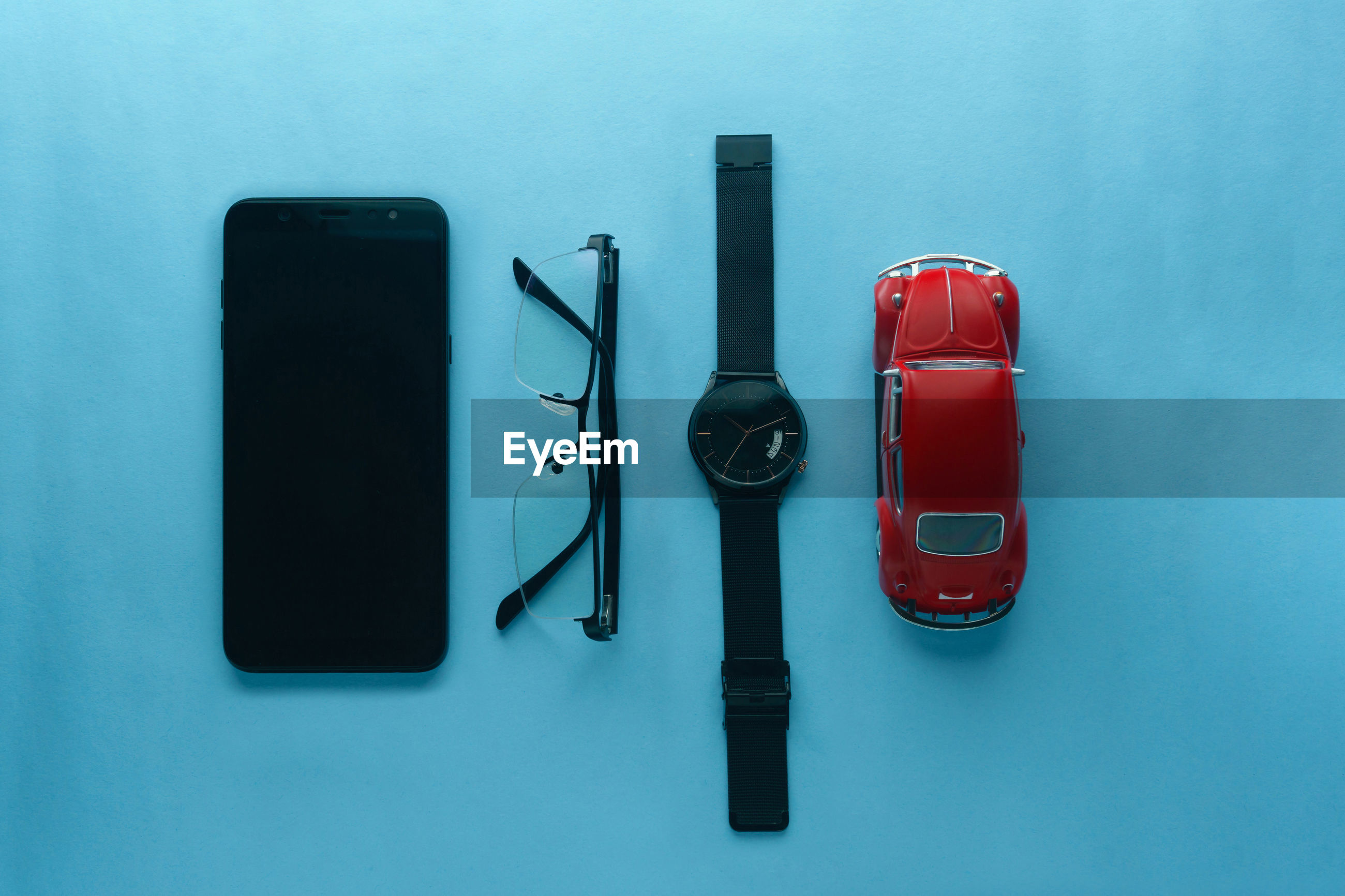 Directly above shot of gadget, eye-glasses, watch and toys on table against blue background
