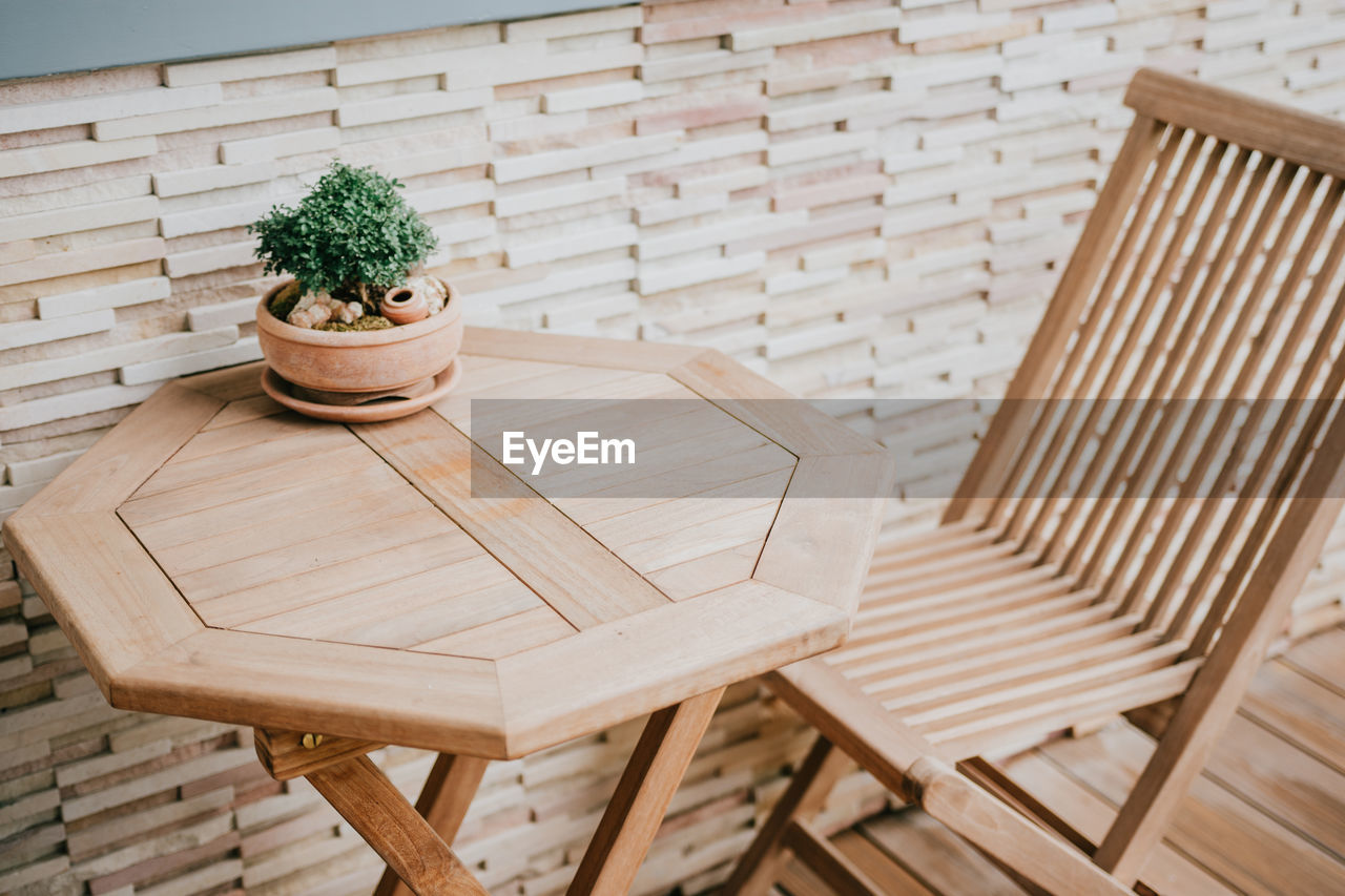 wood - material, seat, table, chair, wicker, potted plant, indoors, no people, plant, brown, basket, focus on foreground, brick, absence, close-up, empty, high angle view, nature, still life, container, flower pot
