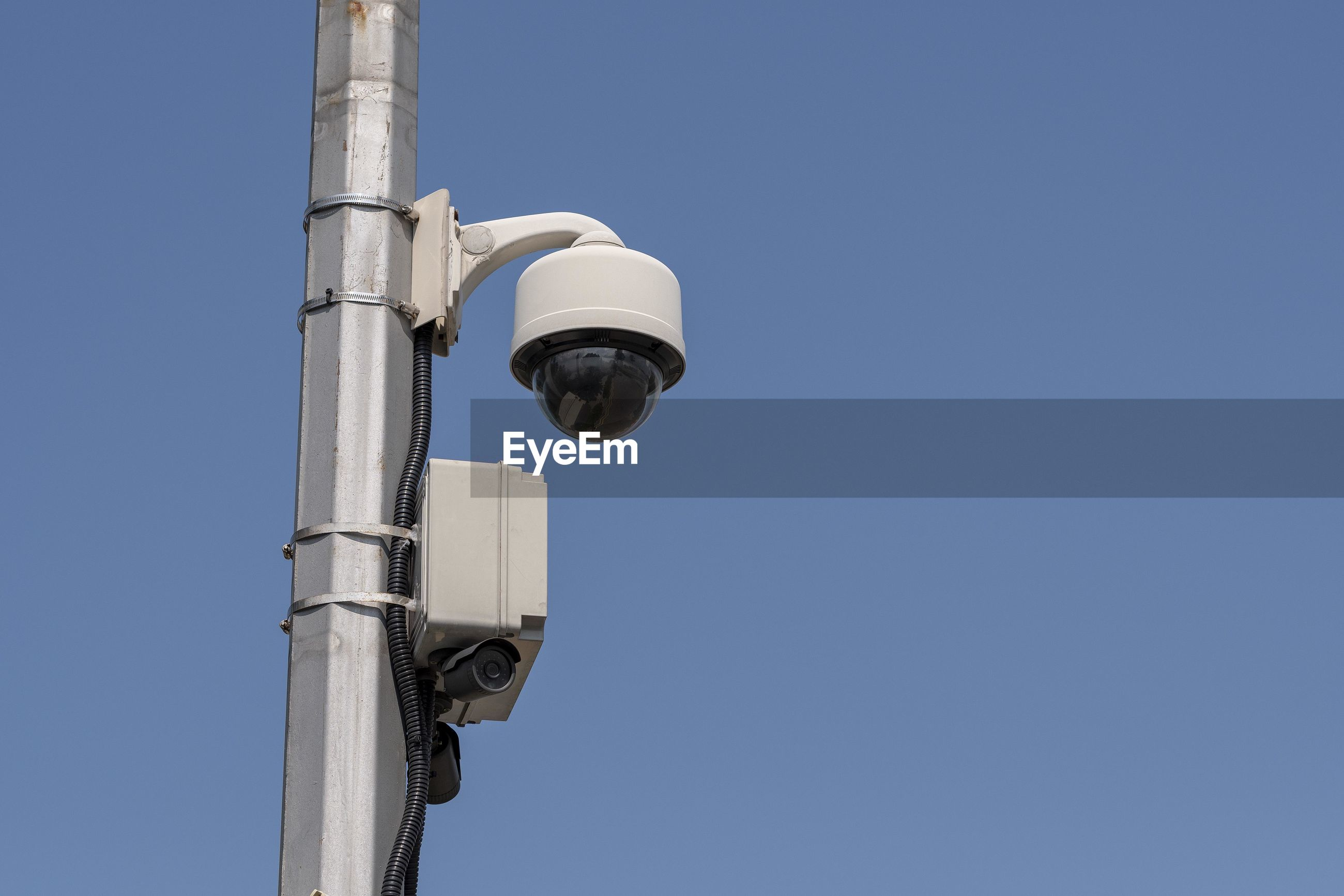 Low angle view of security camera against clear blue sky during sunny day