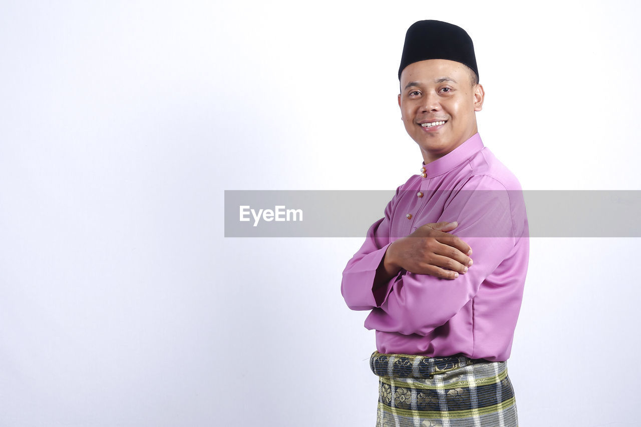 Portrait Of Smiling Man In Traditional Clothing Against White Background