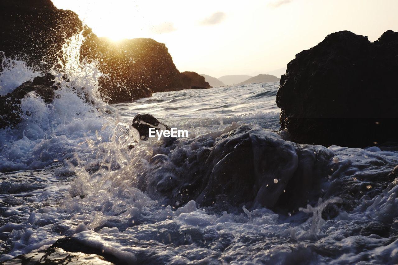 Sea waves splashing on rocks during sunset
