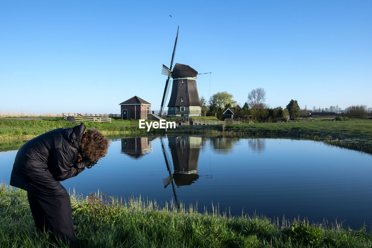 Person photographing by lake against windmill and blue sky
